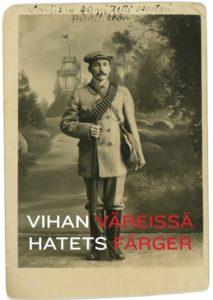 Mustavalkoinen valokuva. Aseistettu mies seisoo Loviisan Kukkukiveä esittävän kulissin edessä. Teksi valkoisella ja punaisella: Vihan väreissä.