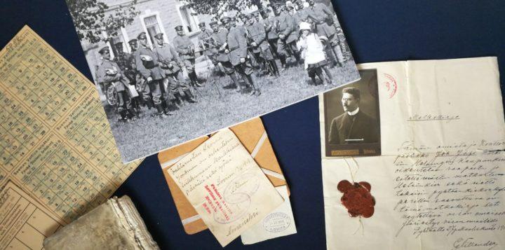 museoesineitä, vanhoja asiakirjoja ja mustavalkoinen valokuva jossa sotilaita