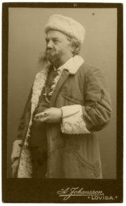 VAnha kuva, jossa viiksekäs mies talviturkissa