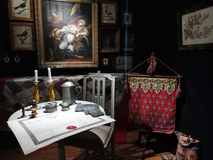 Huone täynnä vanhoja tavaroita ja tauluja