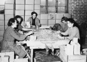 Naisia pöydän ääressä pakkaamassa puisia puikkoja rasioihin.