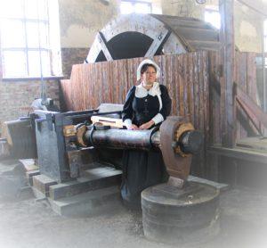 historialliseesn asuun pukeitunut nainen ison vesivasaran vieressä