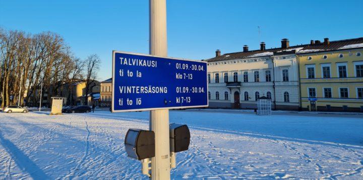 Kyltti talviajoista Loviisan torilla. En skylt om vintertider på Lovisa torg.